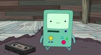S3e19 BMO sitting next to a videotape