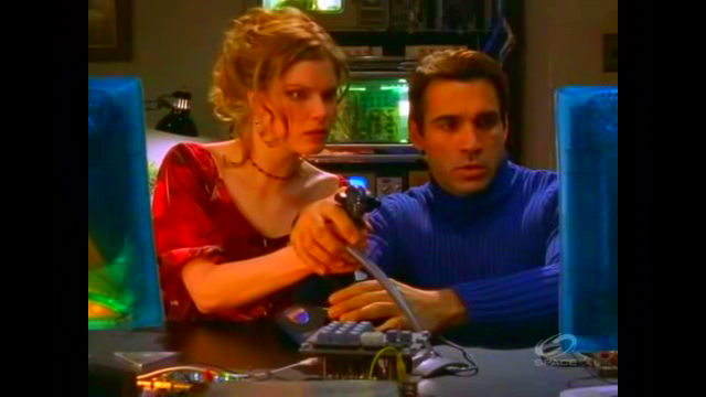 File:Cole shows Mel how to use the camera onscreen..png