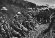 Black-and-white photo of two dozen men in military uniforms and metal helmets sitting or standing in a muddy trench.