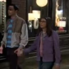 Amy holds Sheldon's hand as an