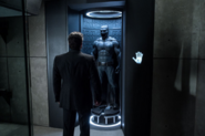 Bruce Wayne standing by the Batsuit