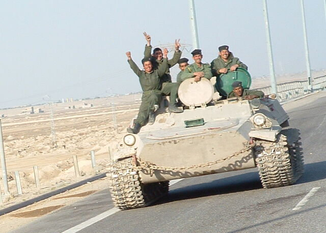 File:Iraqi military men riding on tank.jpg