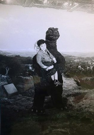 File:ShoshingekiGoji holds a kid.jpg