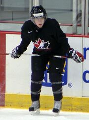 A Caucasian teenage ice hockey player. He stands crouched over towards the ice with his stick resting laterally on his thighs. He wears a black jersey with a stylized maple leaf logo.