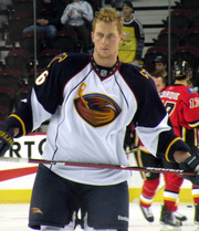 An ice hockey player stands directly upright holding an ice hockey stick horizontally across his stomach. He is wearing a no helmet and is wearing a black and white uniform with a large orange bird with a ice hockey stick on his chest.