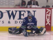 Hockey player in blue Vancouver uniform and goaltender's gear. He is crouched on the ice, legs split far apart.
