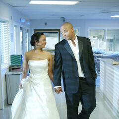Turk and Carla walk the hallways of Sacred Heart in their wedding attire