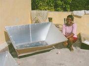 Haiti woman tests reflectors for Dakota Sunstove