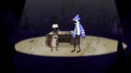 S3E34.179 Mordecai and Rigby Next to a Desk