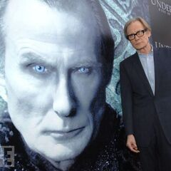 Bill Nighy in front of a large poster of himself as Viktor.