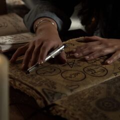 Davina studying Esther's grimoire writing down her own
