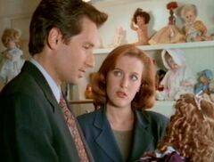 Dana Scully watches Fox Mulder holding a doll