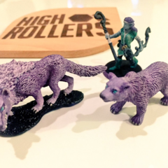 Miniatures are used to depict characters on a map. These are miniatures of Elora (clockwise from left: dire wolf, Elora, bear), pictured alongside a fan-made High Rollers D&D coaster.