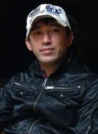 A photograph of a Japanese man wearing a baseball cap.