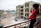A Syrian girl waves from the balcony of an unfinished apartment block in northern Lebanon (11173940763)