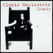 """A barefoot white-skined woman is sitting on a big chair with armrests. She rests her right foot on the left armrest, while she crosses her left leg in front of her body. The background is white, and the words """"Alanis"""", """"Morissette"""" and """"Ironic"""" are written in red letters at the upper right corner."""