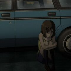 Matsuko sits alone beside the car.
