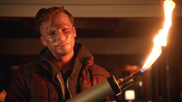 File:Lonnie Machin with a mask and flamethrower.png