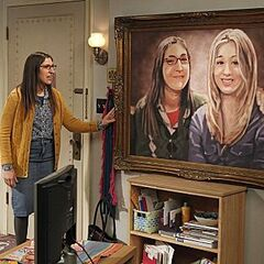 Amy is standing beside the painting, as it hangs on the wall.