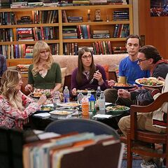 The gang having dinner, not takeout, around the living room coffee table.