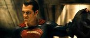 Superman holding Batman's cowl