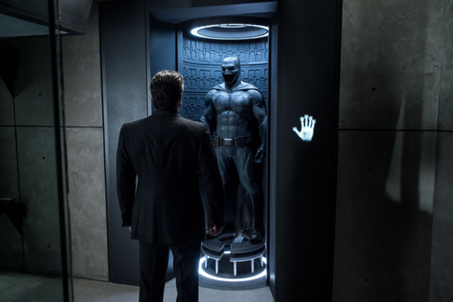 File:Bruce Wayne standing by the Batsuit.png