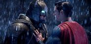 Superman holds back an armored Batman