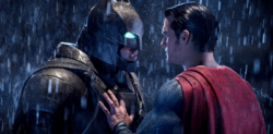 Superman holds back an armored Batman