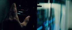 Bruce plugs a hacking device into the LexCorp mainframe