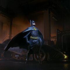 Batman beside the Batmobile.