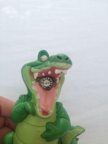 File:Crocodile with an alarm clock toy.jpg