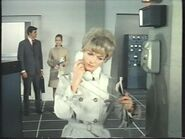 Miss Davies in a rather fetching trench coat (Jan Holden - background Stuart Damon and Alexandra Bastedo) (Large)