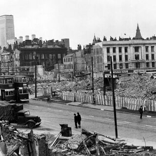 Another photo of bomb damage in the Avenir city centre, this one being taken in 1946, three years after the area was first hit. This photo is of Ville Street, now a main road/ ringway that leads into the city centre, becoming Centenary Green in 1959. The large 'Easterns' building still stands, and the large rectangular spire to the left background is the Tower of Avenir, a famous Avenirian landmark that was unfortunately pulled down in 1974 due to insurance issues, getting replaced with an, albeit taller, much more insignificant concrete tower, which itself was demolished and replaced with the original tower in 2034, with planners calling it 'poetic justice at its finest'.
