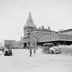 Northern Heights Station on Neil Street (behind Belmont Row), which was built due to its counterpart being in an awkward place for a terminal; it found itself being ironically superior in terms of its terminals, having a longer train line, more advanced carriages, and more places to go to. At the time of this photo, the area of Northern Heights was still being flourished, and notably less characterful. Trees now line the streets, and cobblestone paths and original lamp posts are ubiquitous on the street. Notwithstanding this, most of the buildings have been cleared, as they lacked the grandeur the rest of the place did. The Train Station was designated defunct by the improval of the other, too, and was converted into a small shopping square, with much of the original wings facing reconstruction.