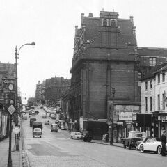The entrance from the High Street crossroads to East Street, when the road was undergoing some major redevelopment at the top; as you can see from the side of the prominent building in the centre, buildings are being demolished, due to their small size; the painted ones suffered a similar fate. To the left, the site has already been cleared, with plans for a new car park being approved. In 2034, these changes were undone, though the small shops were not revived—instead, larger ones were put up.