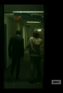 Strand and Nick make their way along a corridor
