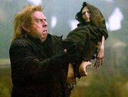 Peter Pettigrew holding Voldemort's rudimentary body.jpg