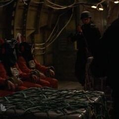 Second row of prisoners seated (seated and offscreen are Tracy and Hiro)prisoners shown are male fugitive(or Flint Gordon),female fugitive 2 and Sparrow Redhouse from left to right