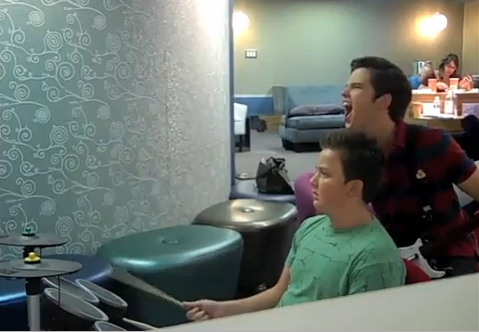 File:Noah playing drum hero while Nathan is screaming.png