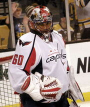 Hockey player in white Washington Capitals uniform with the number sixty on it, and goaltender's gear. He stands at ease in front of goal, hands by his side, and looks downward.