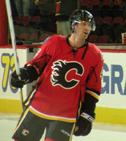 "Hockey player in red uniform, with a ""C"" in the middle. He leans to his left, holding his stick by his side."