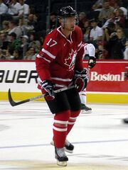 Hockey player in red uniform. He holds his stick as if preparing to hit the puck.