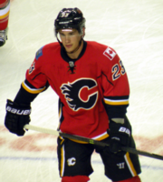 """Upper body of a hockey player who is skating up the ice.  He is in a red uniform with black and yellow trim, and a stylized """"C"""" logo on his chest."""