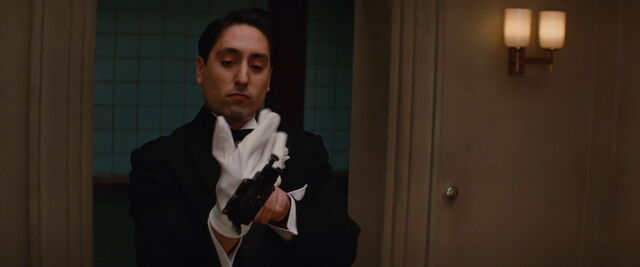 File:Omar puts his OSS Glove Pistol.jpg