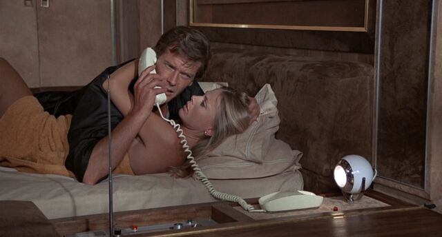 File:TMWTGG - Bond and Goodnight receive a call from M.jpg