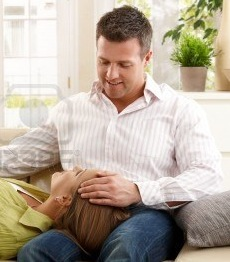 File:7136712-mid-adult-woman-expecting-baby-lying-on-sofa-in-smiling-man-s-lap-man-stroking-her-head-other-hand-o.jpg