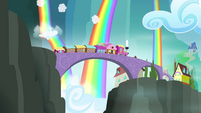 Train moving with rainbow-colored waterfalls in the background S4E10