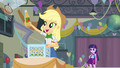 Applejack picks up a cider bottle EG.png