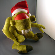A green plush toy of a Vortigaunt sits against a gray wall. The toy is wearing a Santa Claus hat, leaving only the dominant red eye visible.