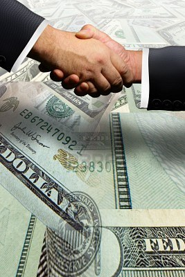 File:2834751-two-business-men-shaking-hands-over-a-money-transaction.jpg